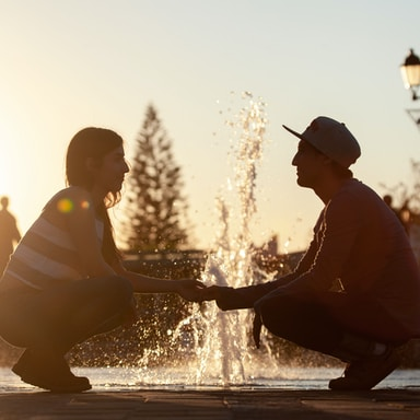 man and woman sitting on water during daytime