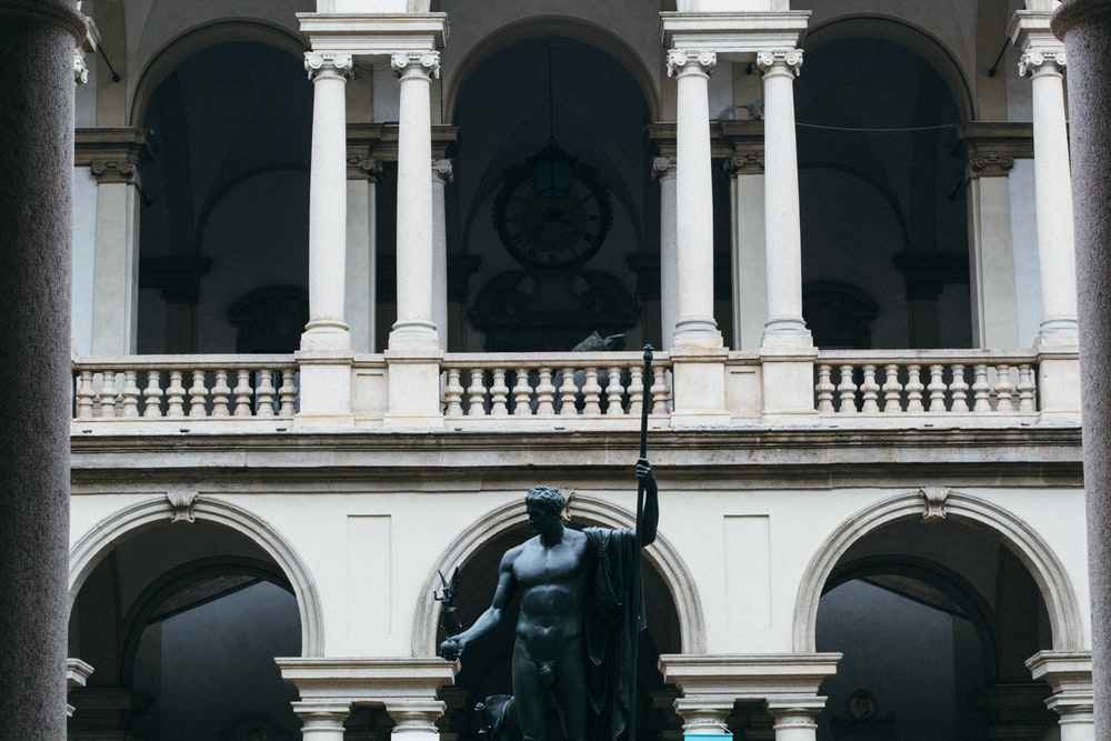 black statue in front of white building