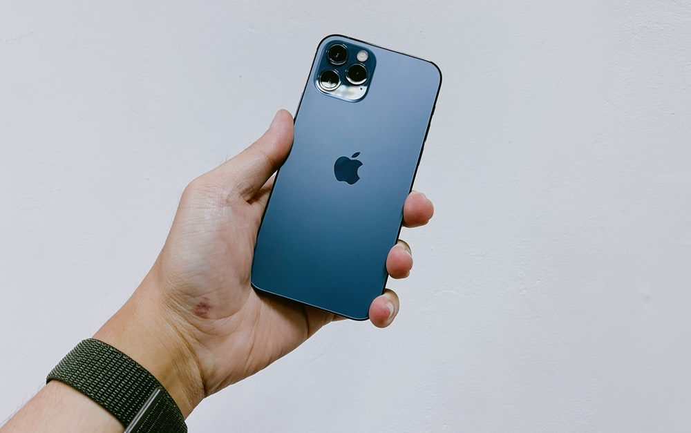 person holding blue iphone 5 c