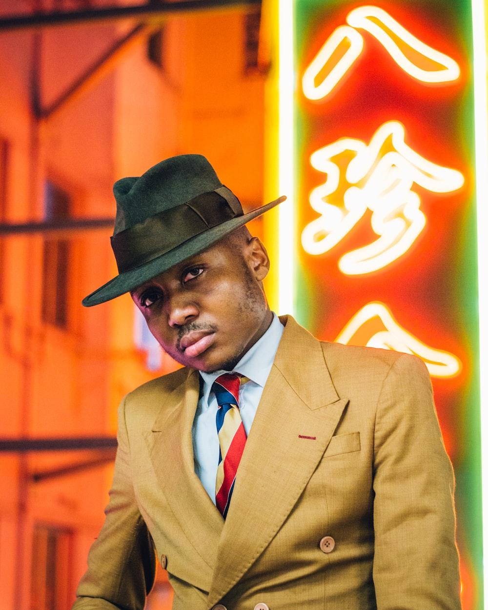 man in brown suit wearing black hat