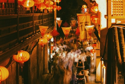 white and red paper lanterns on street during nighttime lantern festival teams background