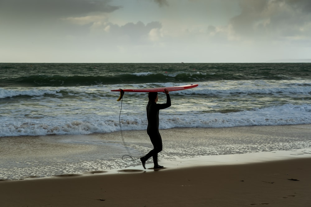 man in black wet suit holding red surfboard standing on beach during daytime