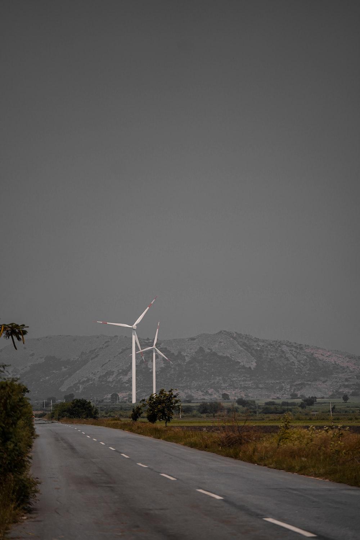 white wind turbines on gray asphalt road during daytime