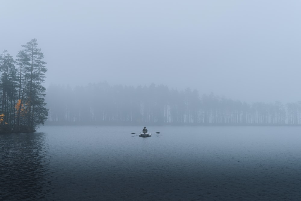 person riding on boat on lake during foggy weather