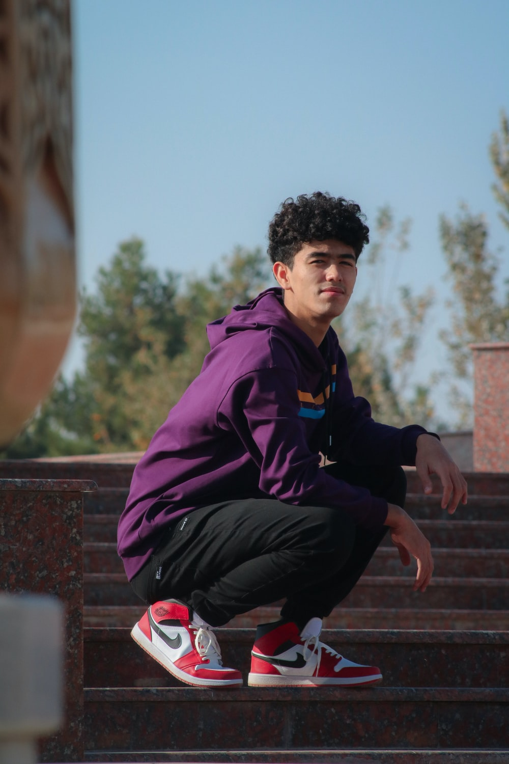 man in purple and black jacket sitting on brown concrete stairs during daytime