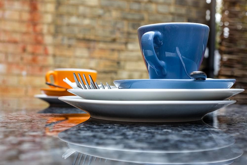 blue ceramic teacup on white ceramic plate