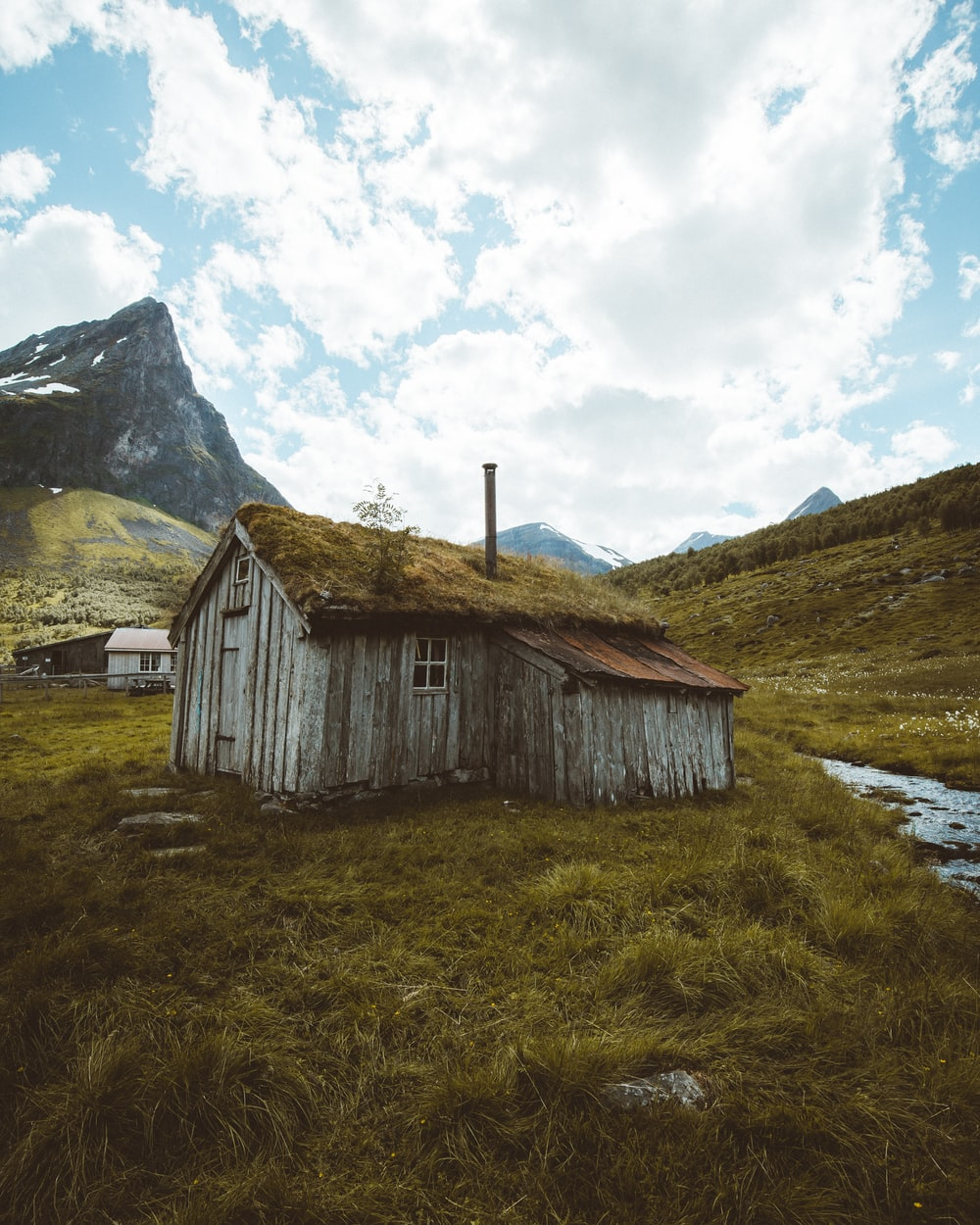 brown wooden house on green grass field near mountain under white clouds during daytime