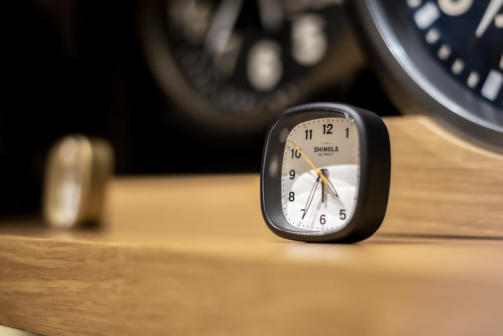 black and white analog alarm clock at 10 00