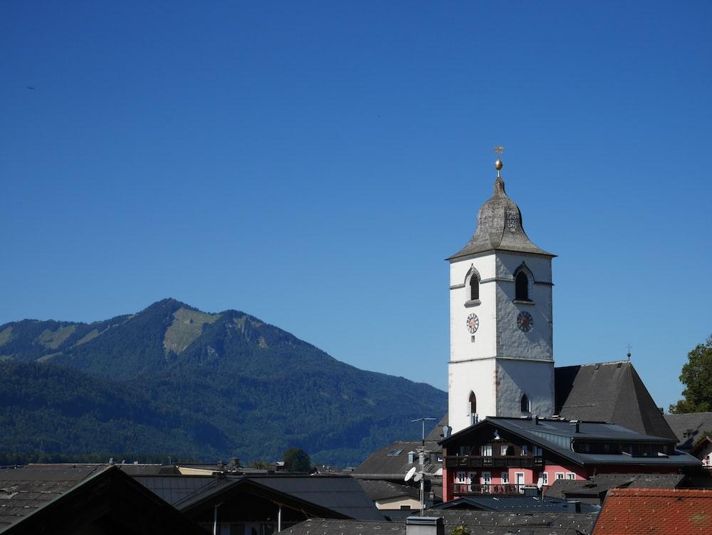 white concrete church near mountain under blue sky during daytime