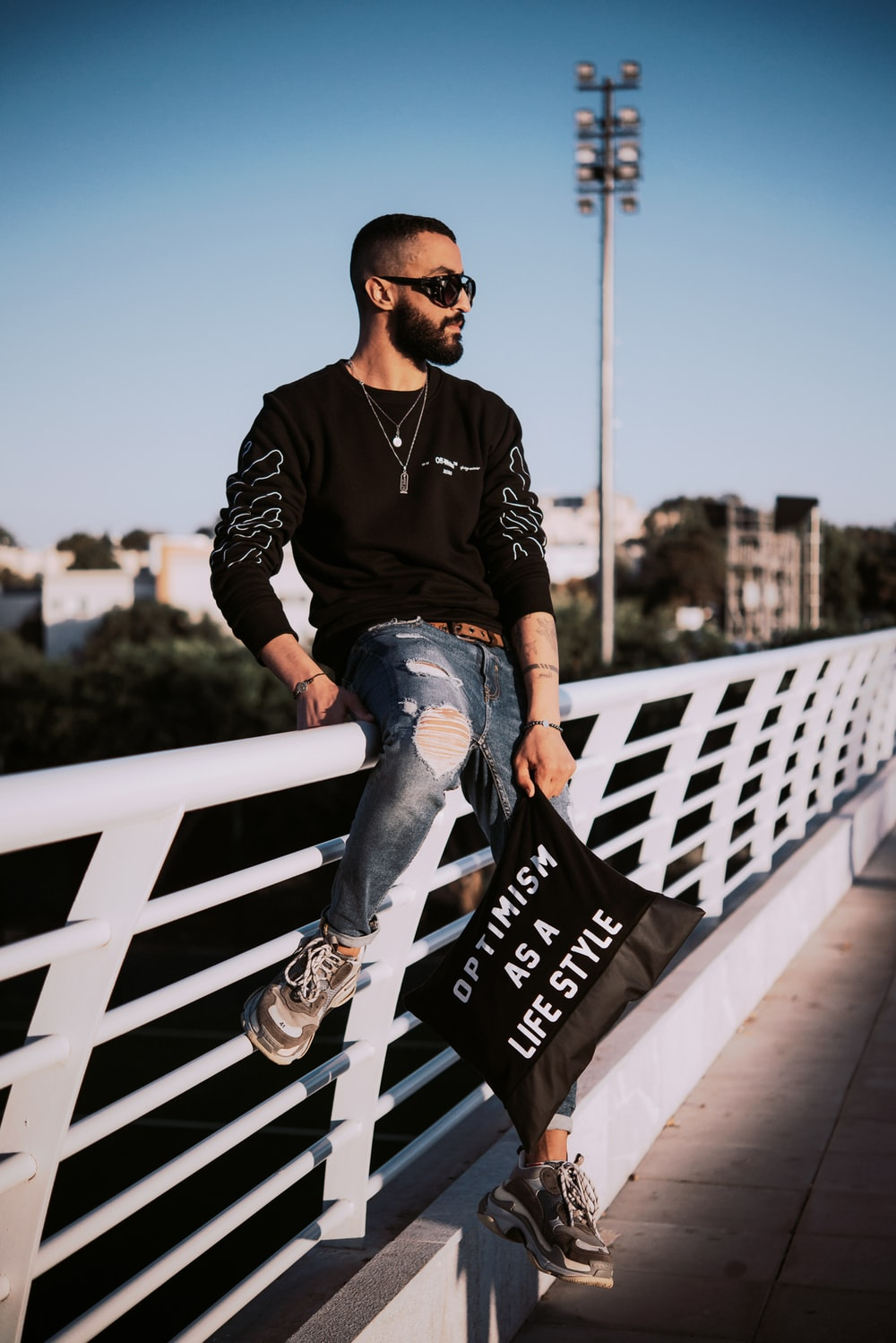 man in black and white long sleeve shirt and blue denim jeans sitting on white wooden