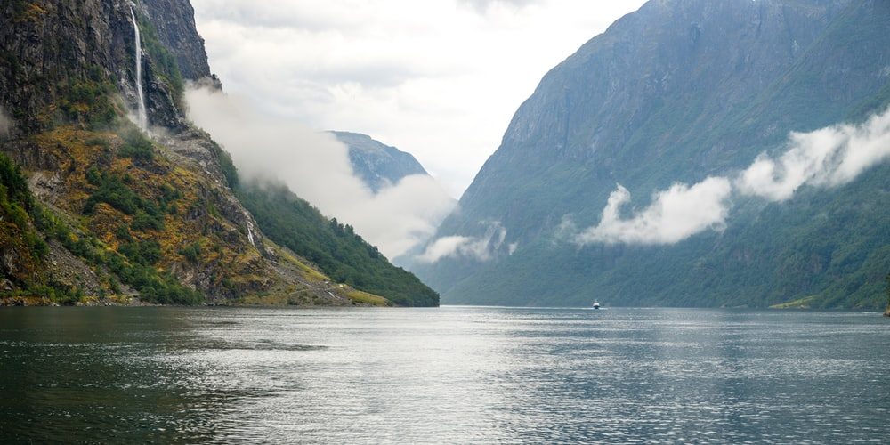 green and gray mountains beside body of water during daytime
