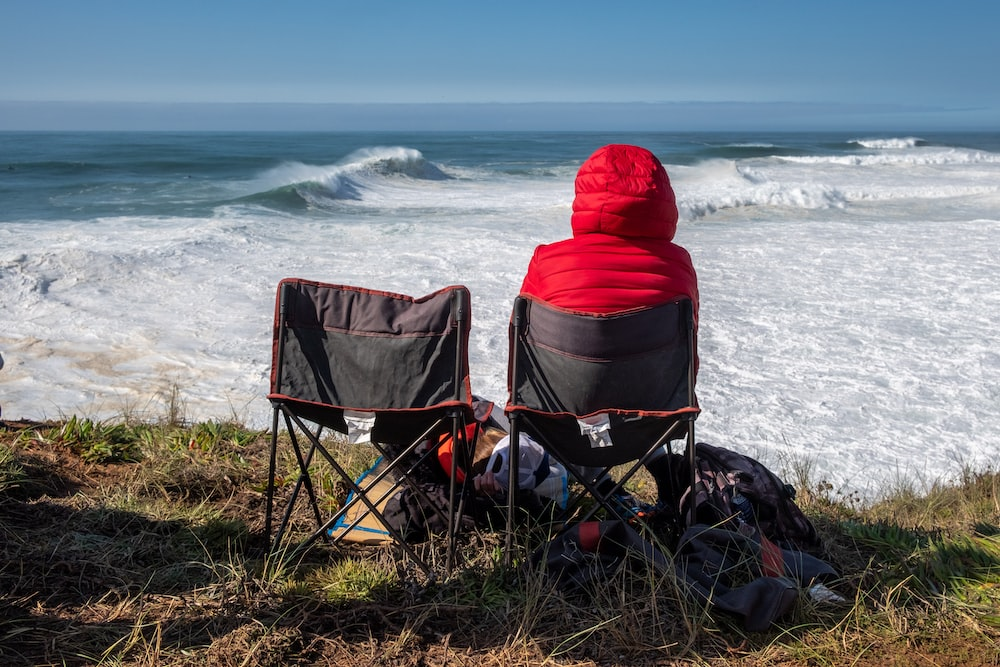 person in red hoodie sitting on blue camping chair on seashore during daytime