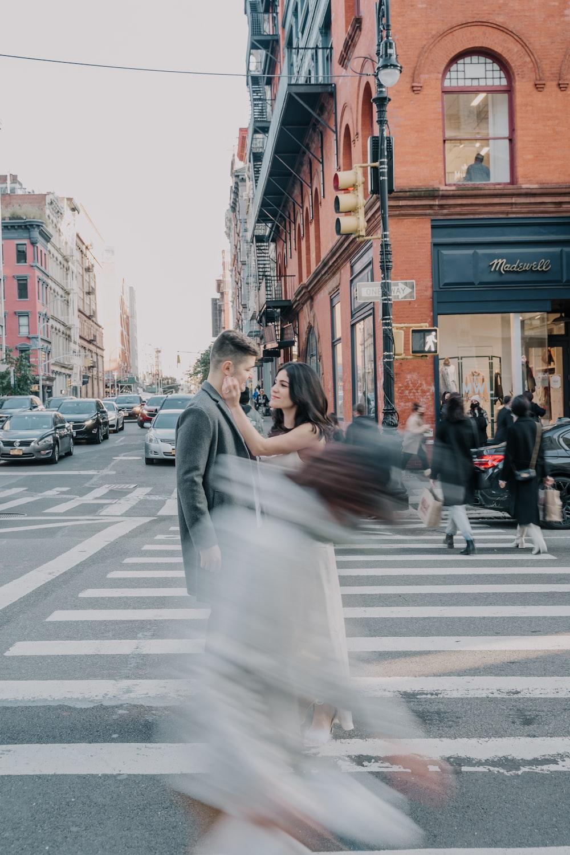 man in gray suit jacket holding woman in white wedding dress walking on pedestrian lane during