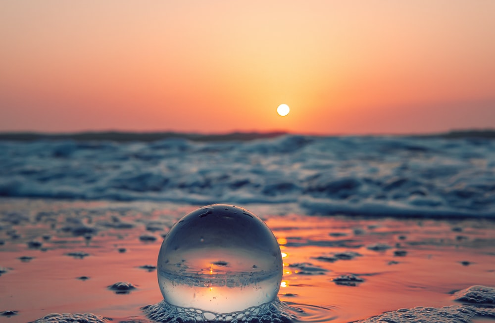 clear glass ball on water during daytime