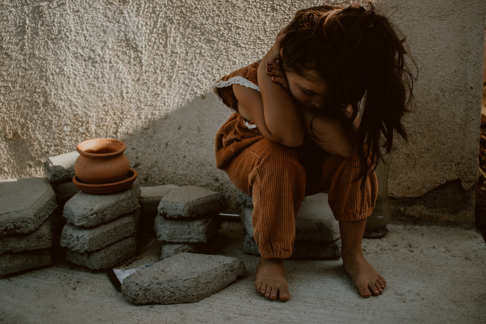 girl in brown dress sitting on gray concrete floor