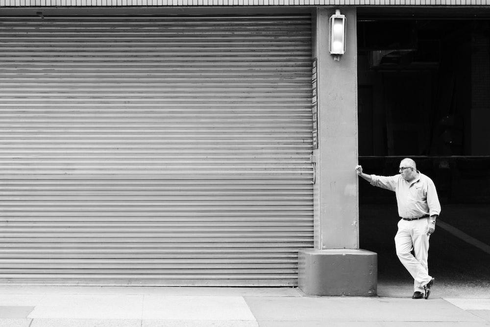 man in white long sleeve shirt and black pants walking on sidewalk during daytime