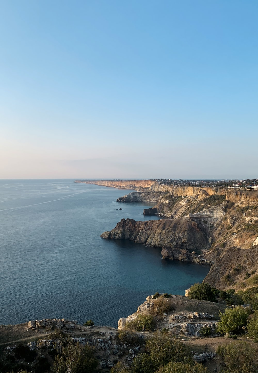 brown and green cliff beside sea under blue sky during daytime