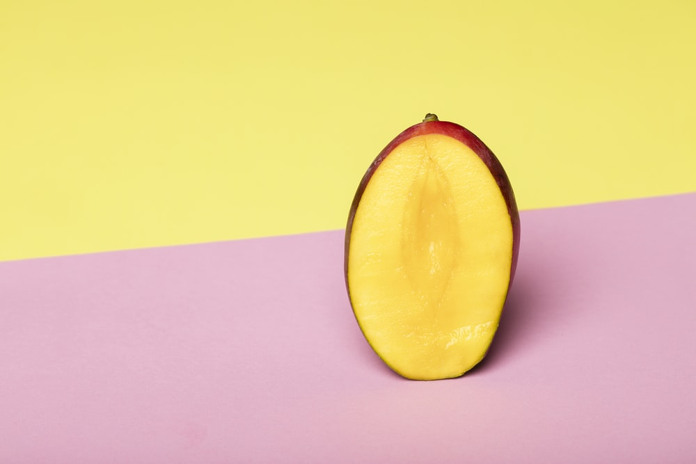 sliced yellow fruit on pink surface