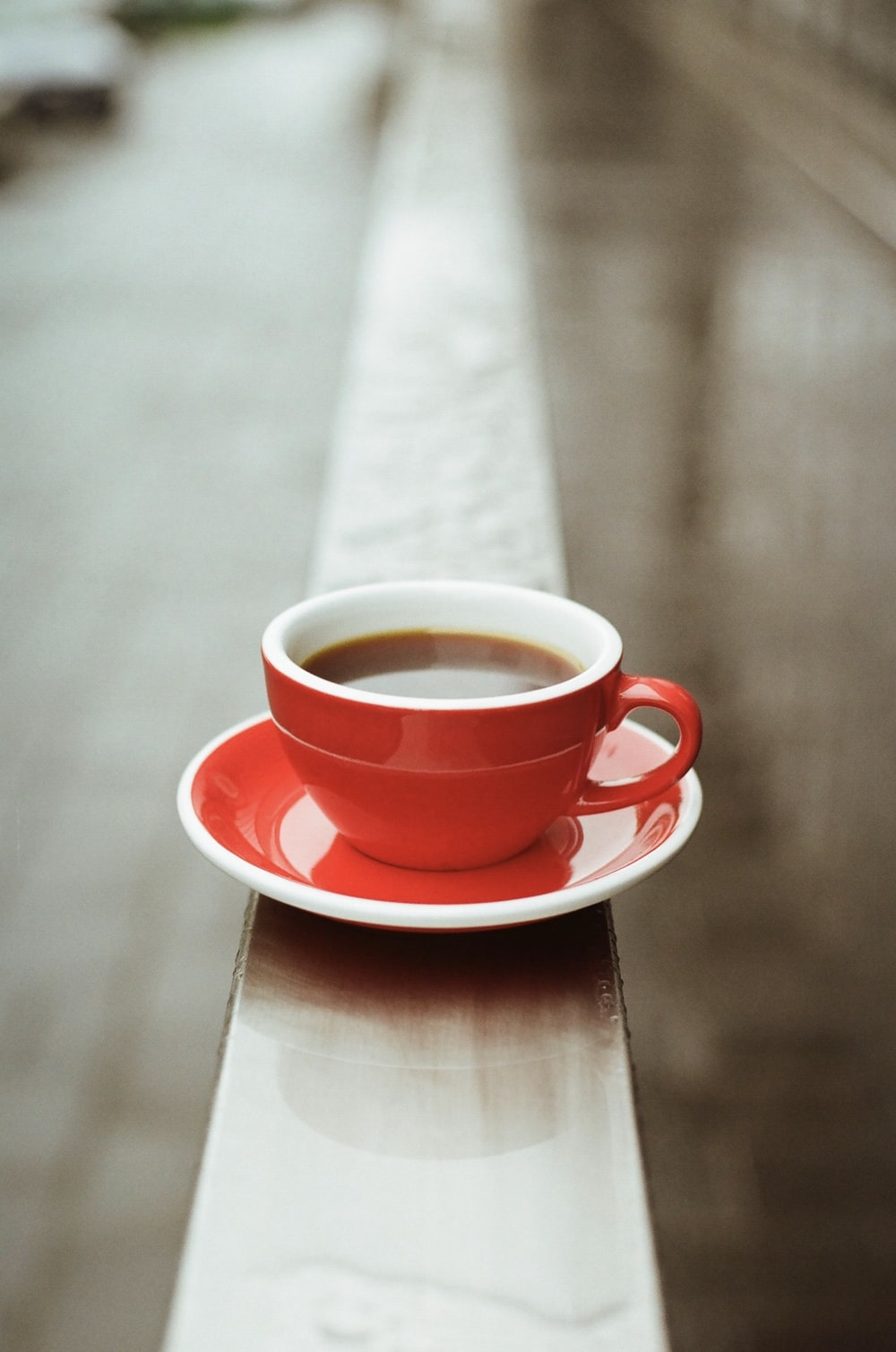 red ceramic teacup on red saucer on brown wooden table