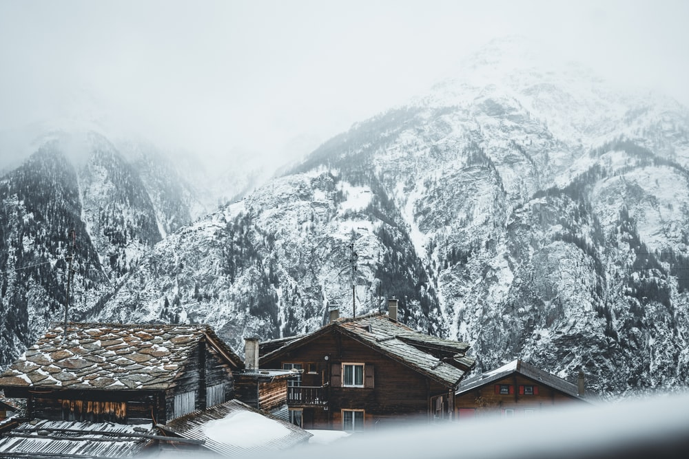 brown wooden houses near snow covered mountain during daytime