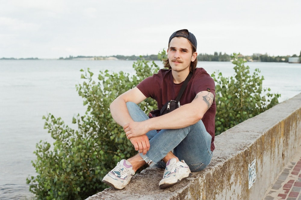 man in maroon polo shirt and blue denim jeans sitting on concrete bench
