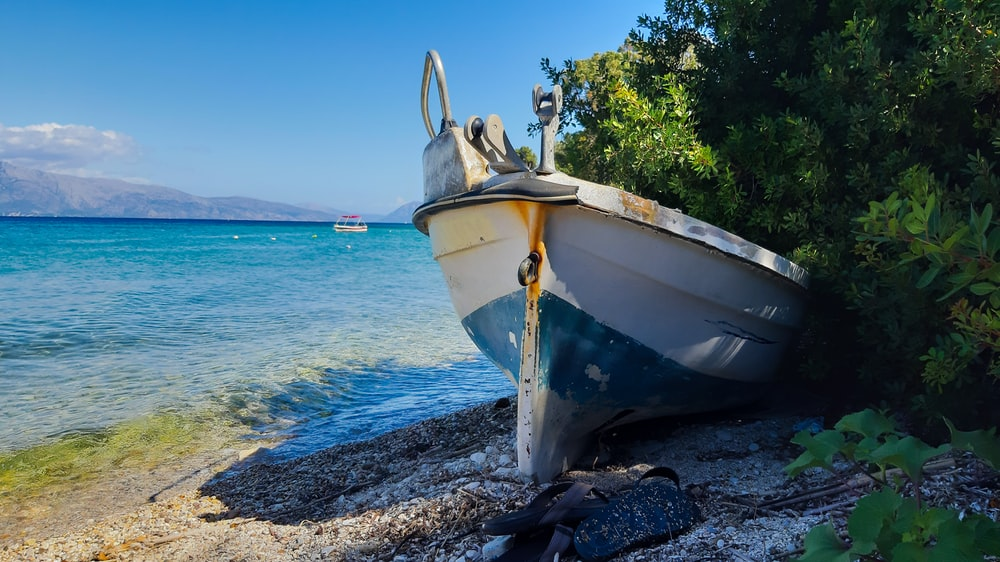 white and yellow boat on shore during daytime