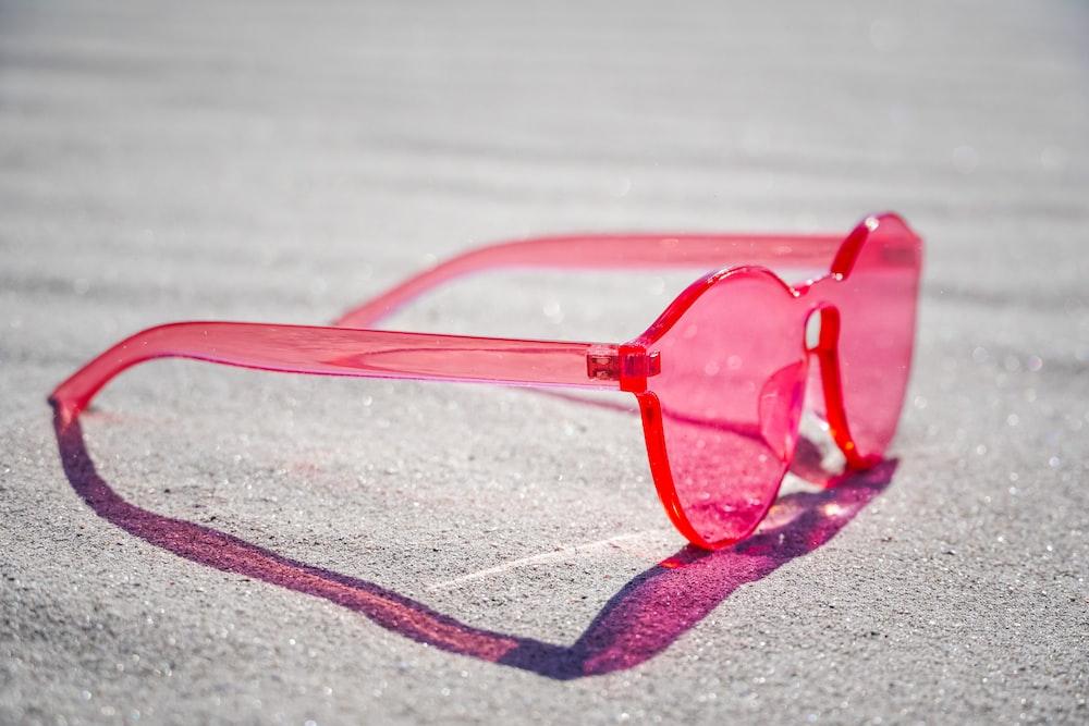 red framed eyeglasses on gray textile