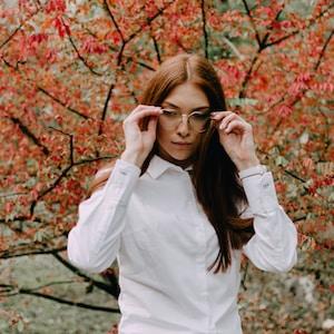 woman in white dress shirt wearing eyeglasses standing near red leaf tree during daytime
