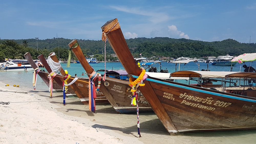 brown wooden boat on white sand during daytime