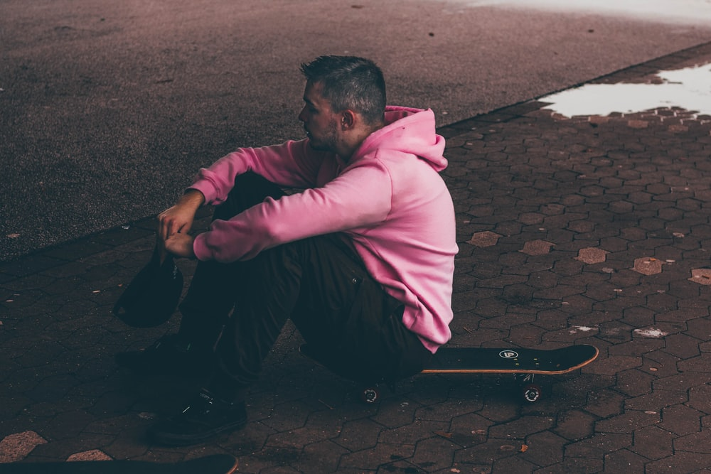 man in pink dress shirt and black pants sitting on brown brick floor during daytime