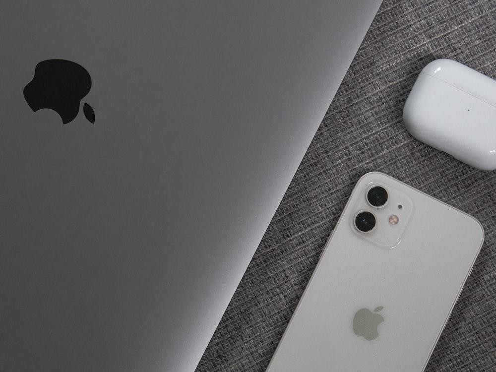white apple remote beside white remote control
