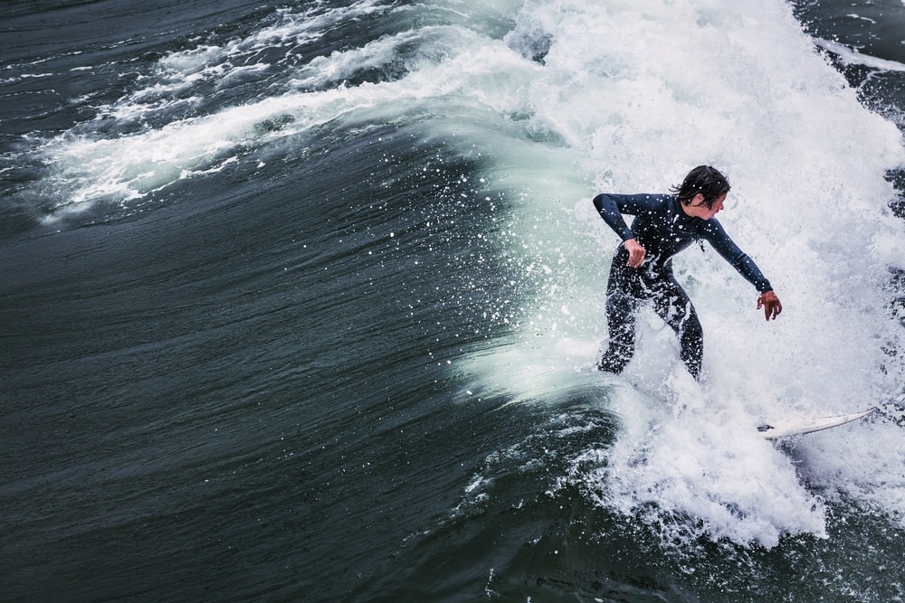 man in black wet suit surfing on sea waves during daytime