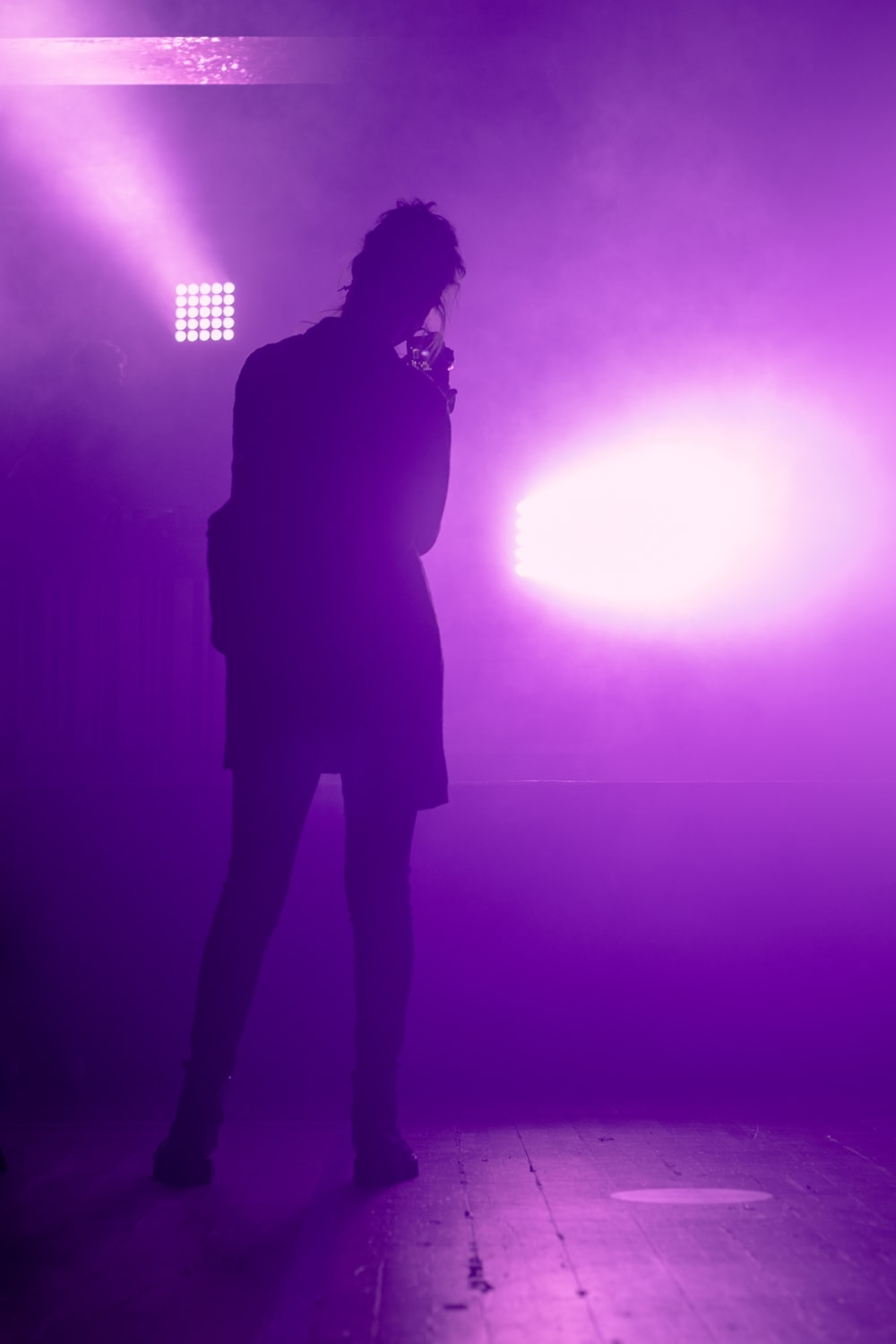 silhouette of woman standing on stage