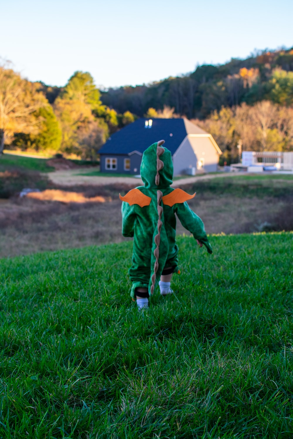 boy in green and orange jacket walking on green grass field during daytime