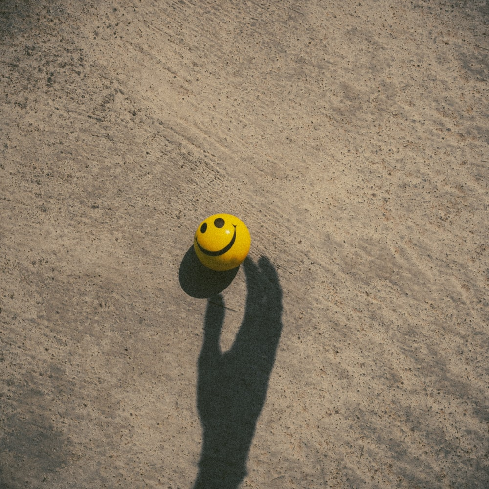 yellow and black soccer ball on brown carpet