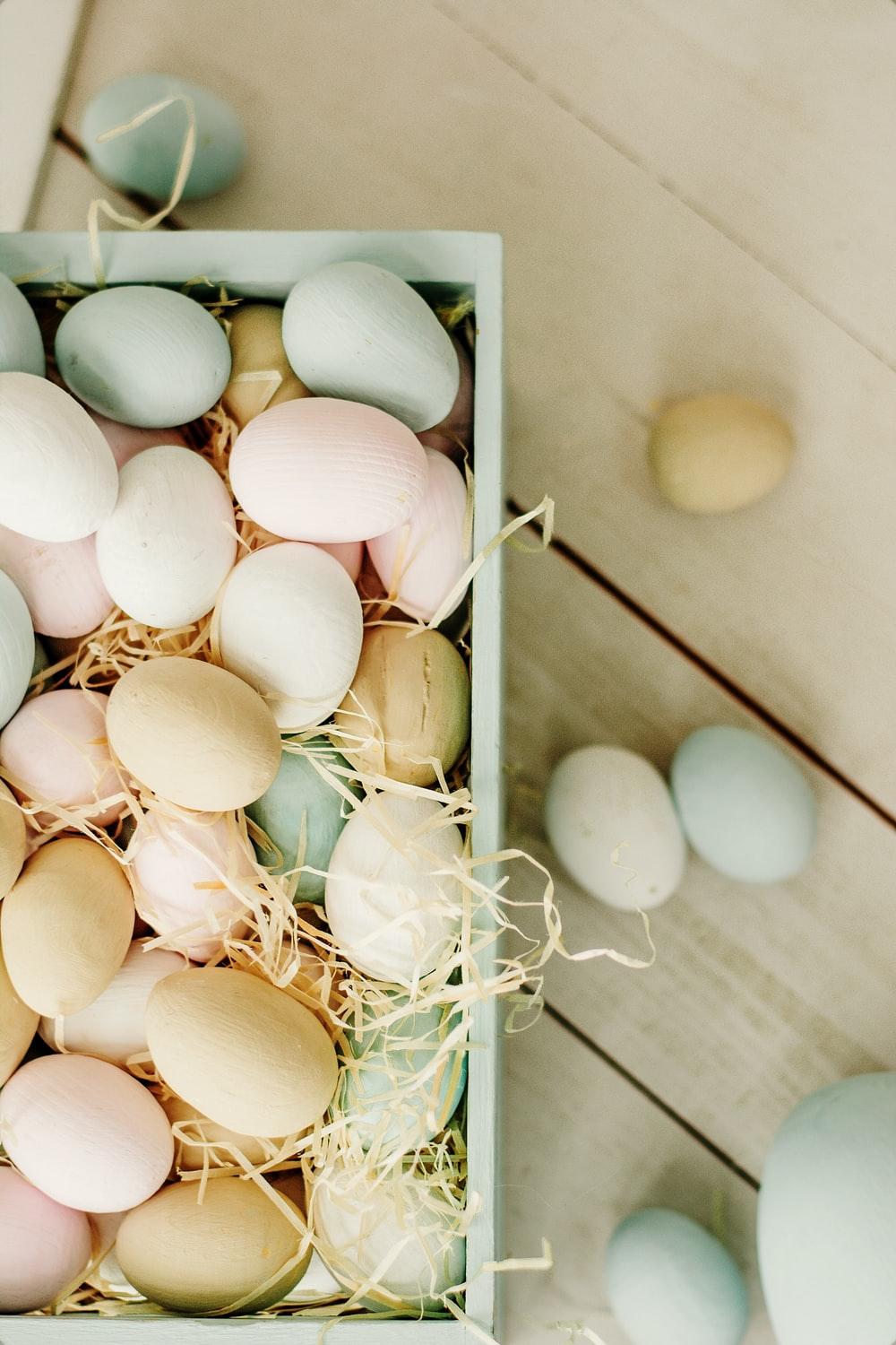 white and brown eggs on white wooden tray