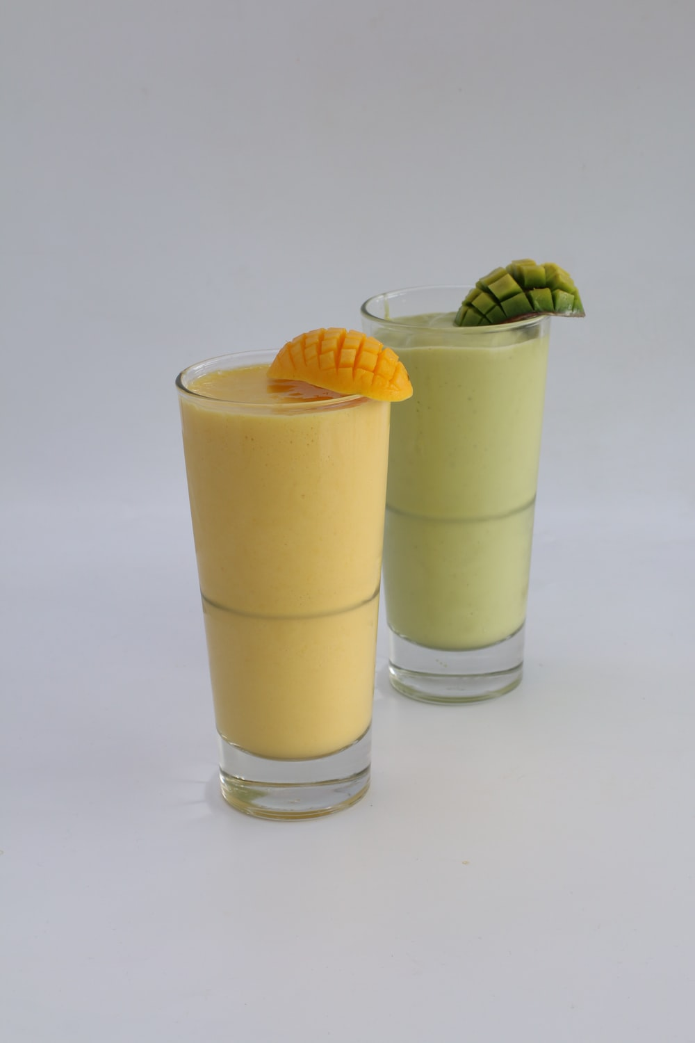 2 clear drinking glasses with yellow liquid