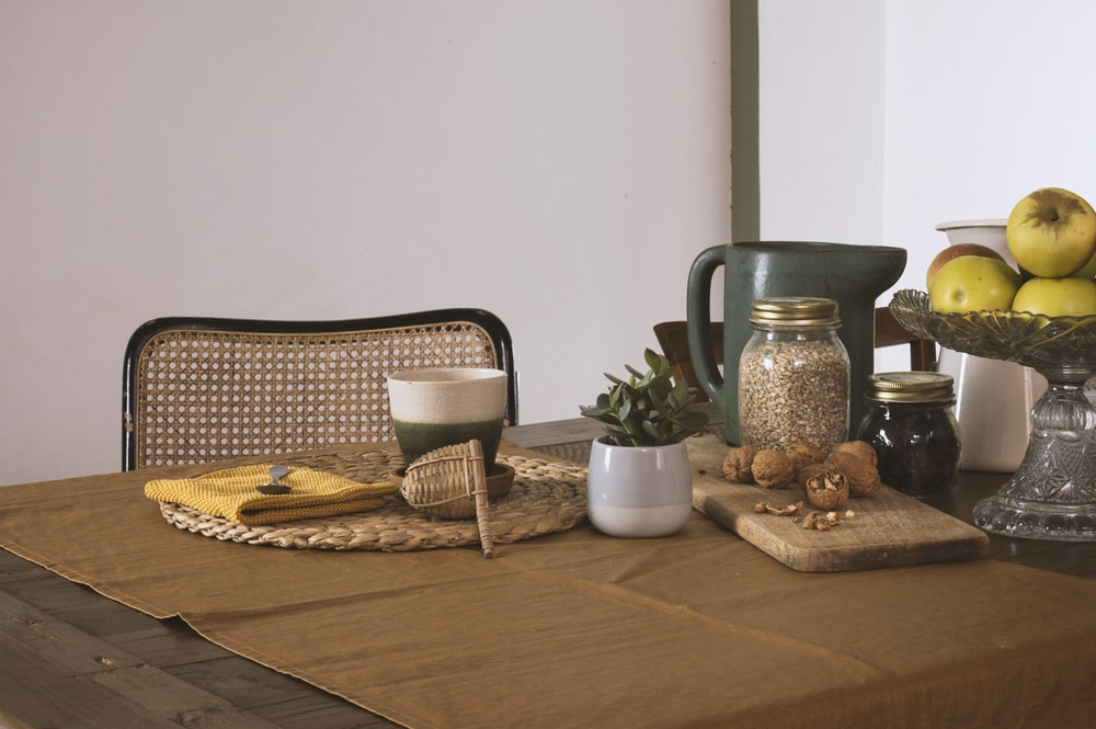 brown wooden table with brown wicker basket and pitcher