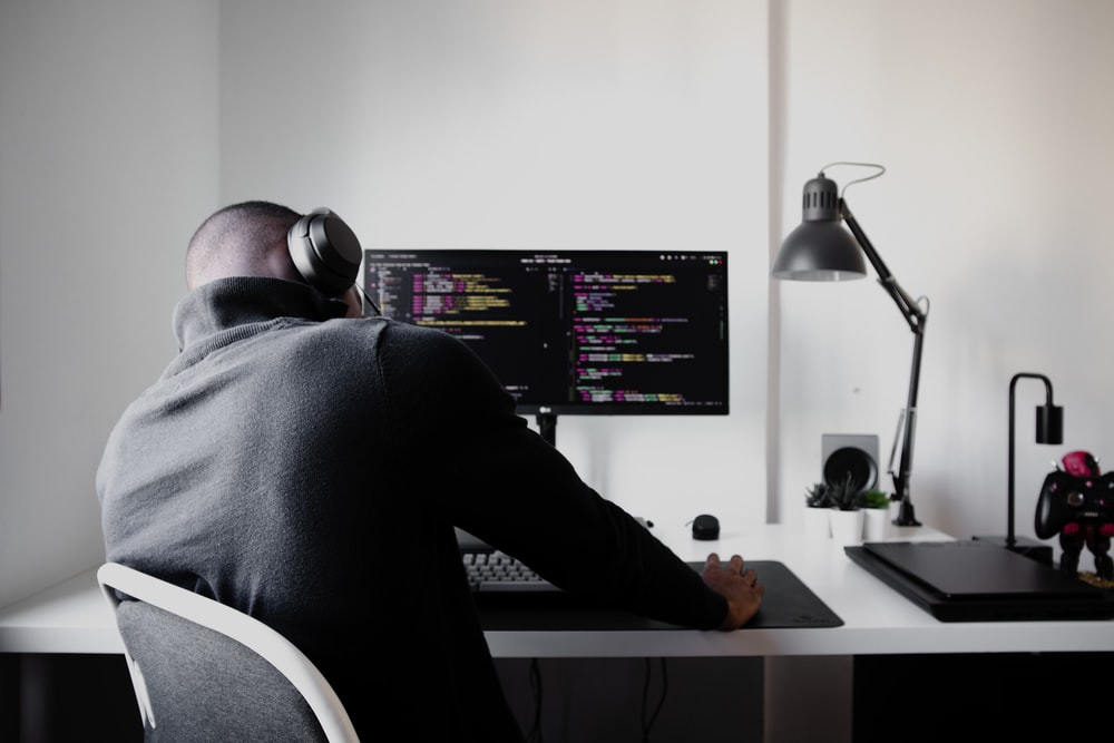 man in black long sleeve shirt sitting on chair in front of computer