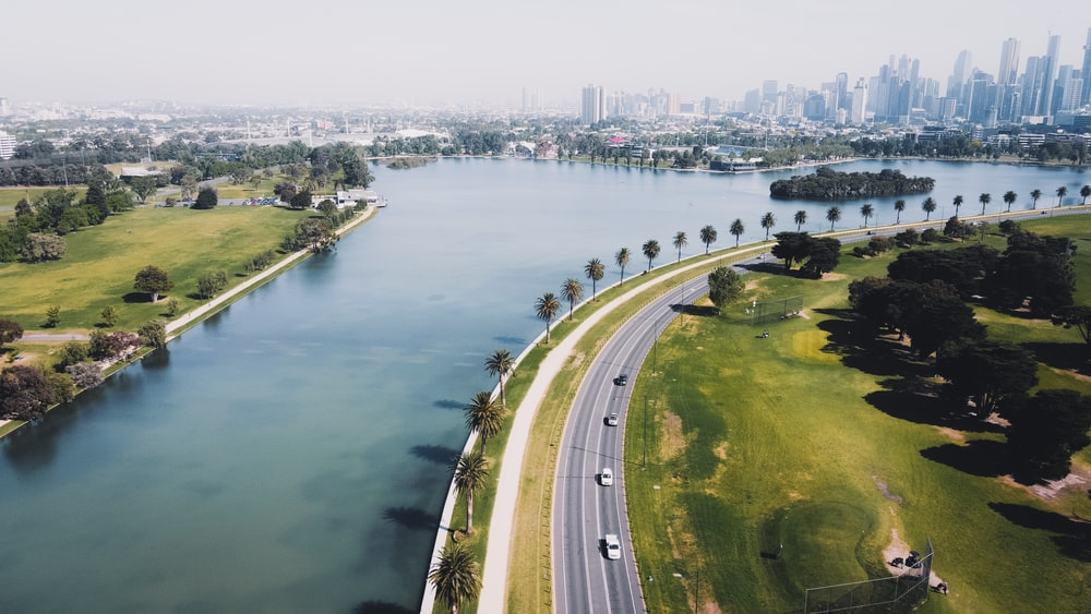 aerial view of highway near body of water during daytime