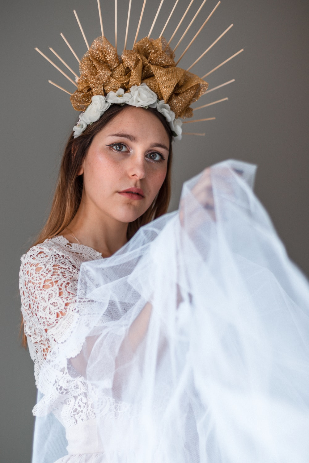 woman in white lace floral dress wearing brown floral head band