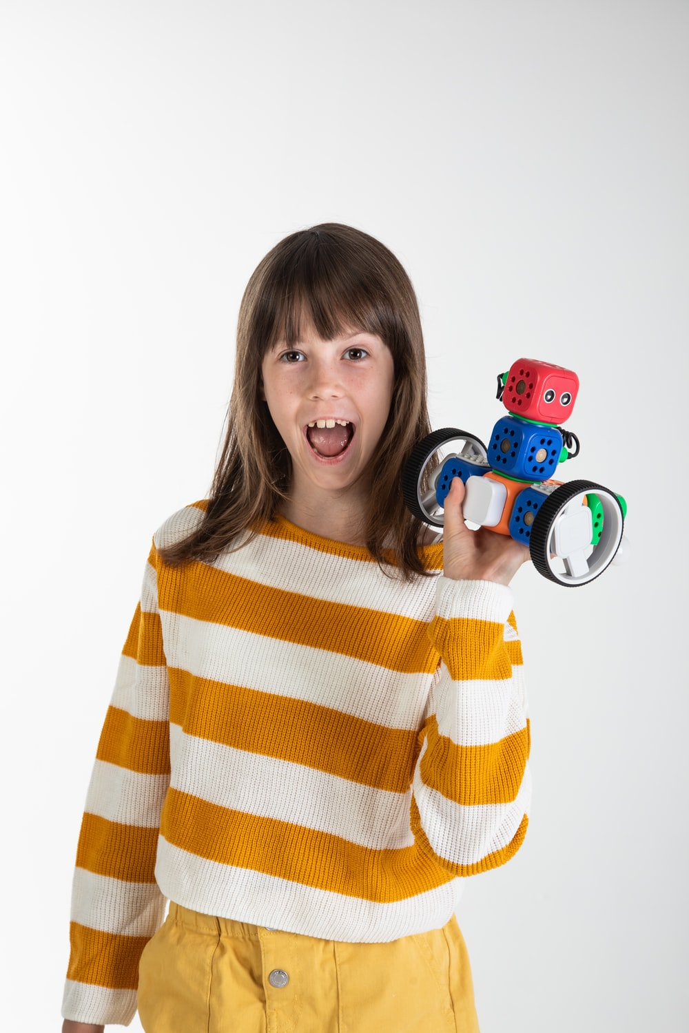 woman in yellow and white striped long sleeve shirt holding red and black toy car