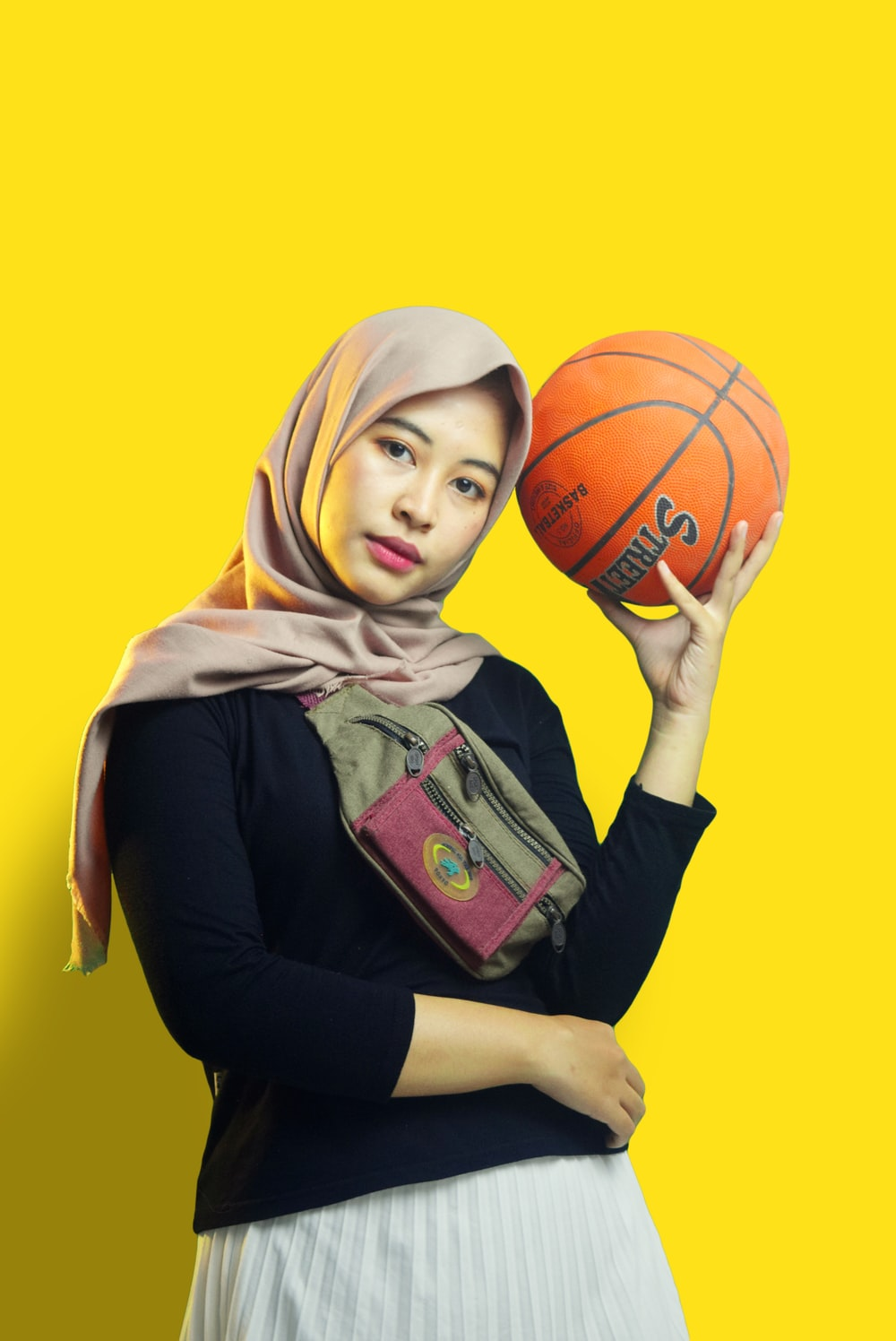 woman in brown hijab holding basketball