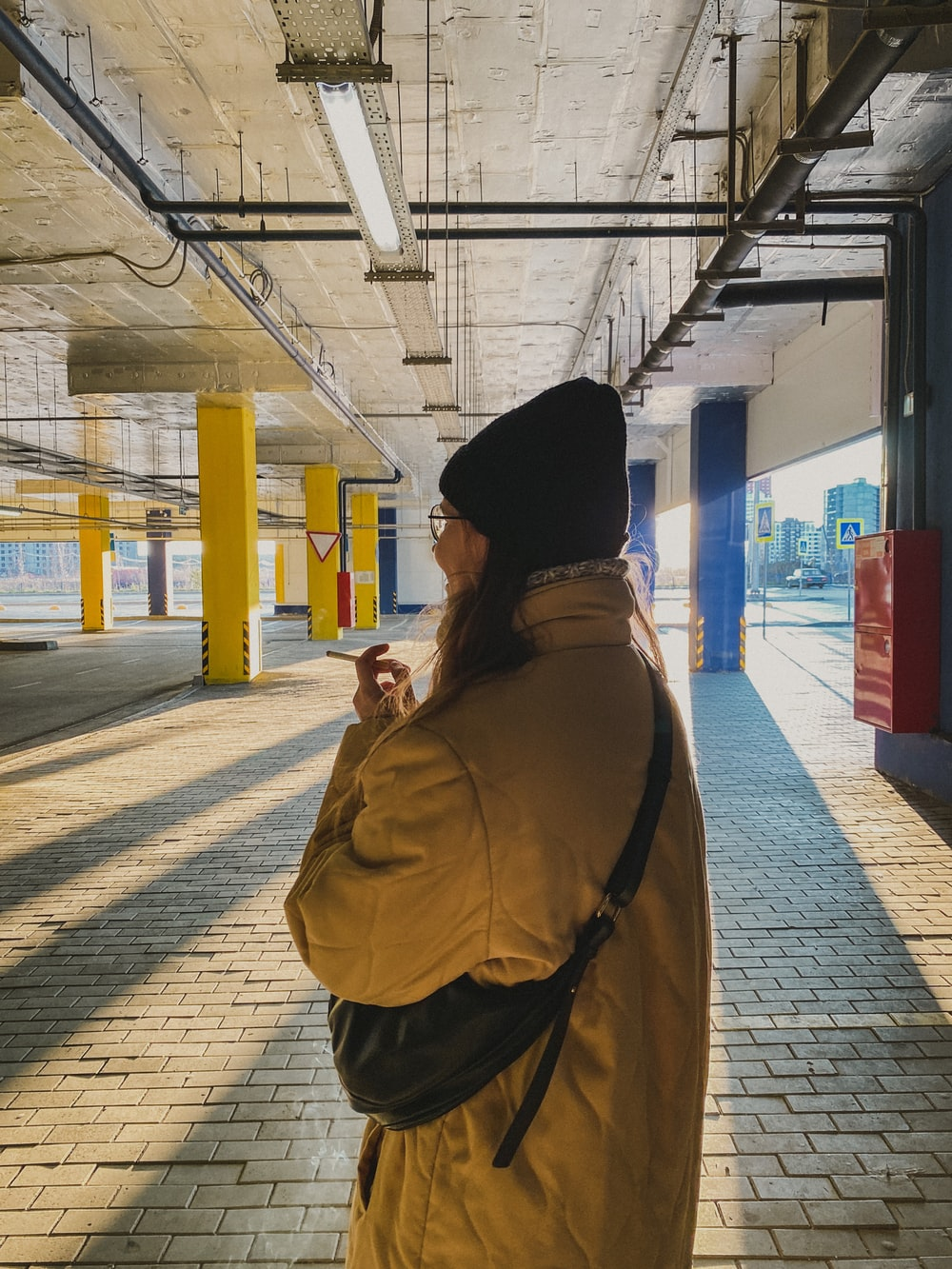 woman in brown coat and black knit cap standing near train station during daytime