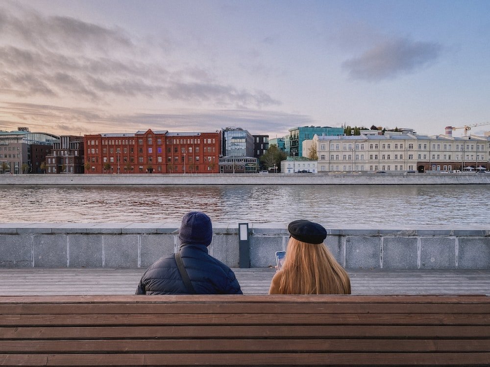 2 person sitting on brown wooden bench during daytime