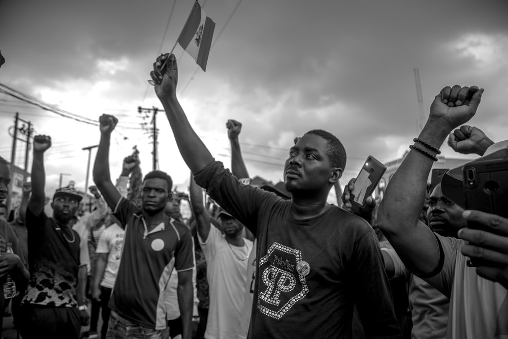 grayscale photo of man in crew neck t-shirt raising his hands