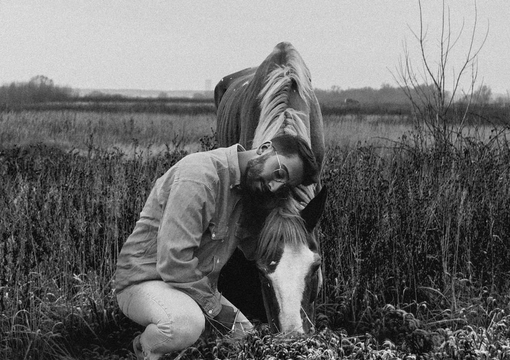 grayscale photo of woman in jacket sitting on grass field