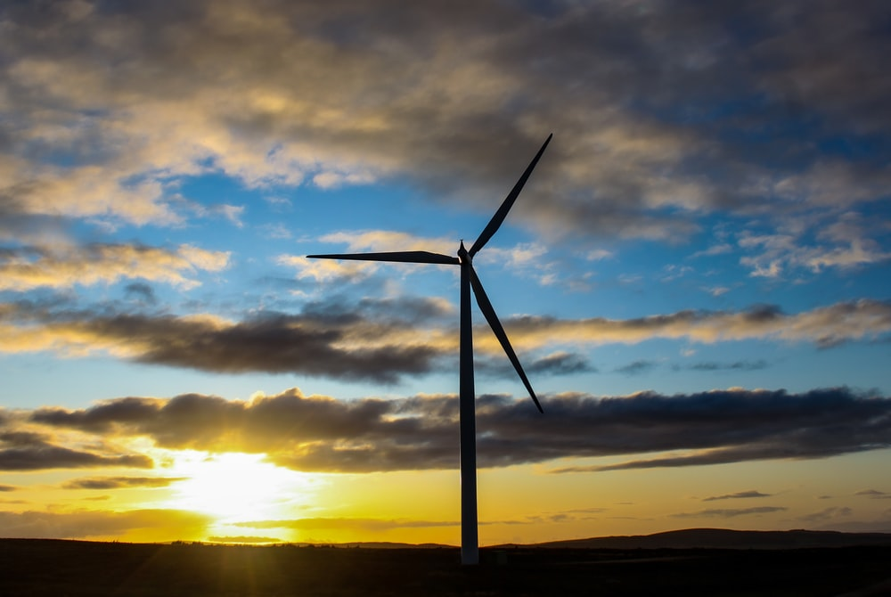 wind turbine under cloudy sky during sunset