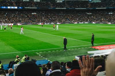 people watching soccer game during daytime real madrid teams background