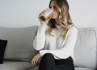 woman in white sweater and black pants sitting on couch